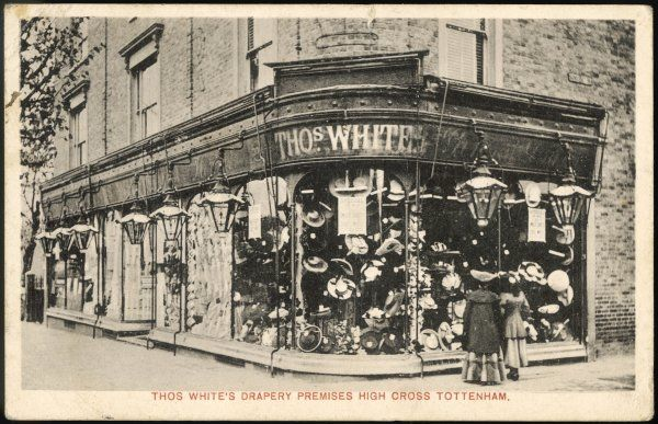 Two ladies pause to appraise the hats in the window of Thos. White's Drapery Premises, High Street, Tottenham