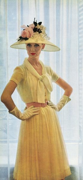 A dress by Pierre Balmain in pale yellow silk chiffon with a matching hat trimmed with roses and white lilac. Date: 1960