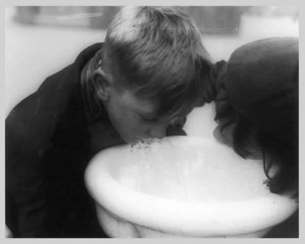 Two children drinking from a fountain