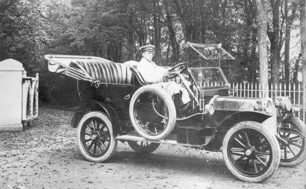 Mr E Codd of Bland Motors, driving an open topped car, probably in Haverfordwest, Pembrokeshire, South Wales. J & G Bland (Motors) Ltd was established in 1875 and is still in existence today