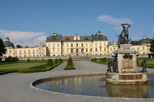 View of Drottningholm Palace and part of the Park, in Stockholm County, Uppland, Sweden, with a fountain in the foreground. The palace was built in the late 16th century and is the private residence of the Swedish royal family