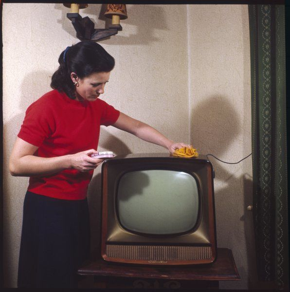 A young housewife lifts up an ash tray as she dusts the television