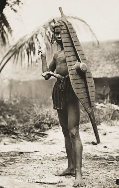 A Dyak warrior chief from Singapore, bearing a fantastic slender leaf-shaped carved wooden shield and carrying a spear, ready to (seemingly) throw at the photographer!