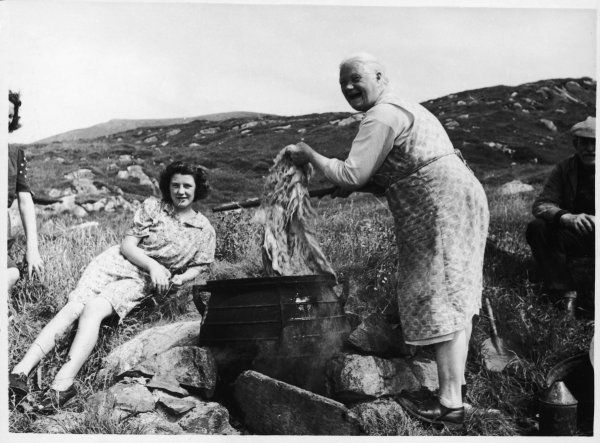 Production of Harris Tweed. An old woman from the island dyes the wool in a cauldron- like vessel which sits on an open fire