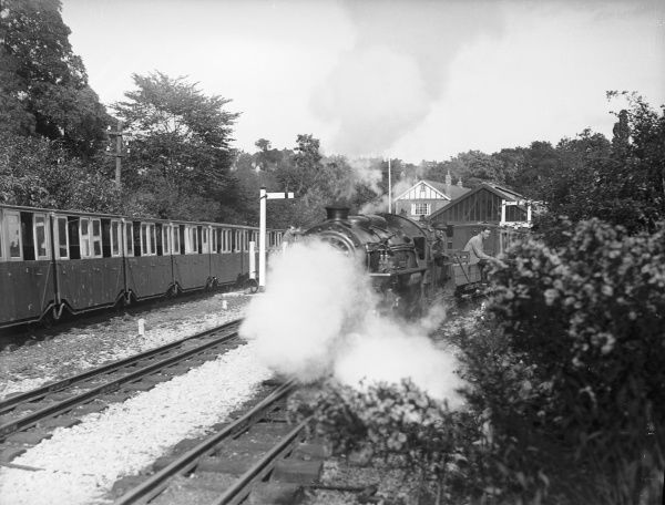A locomotive on the The Romney, Hythe and Dymchurch Light Railway (a miniature railway), Kent, England, pulling out of a station