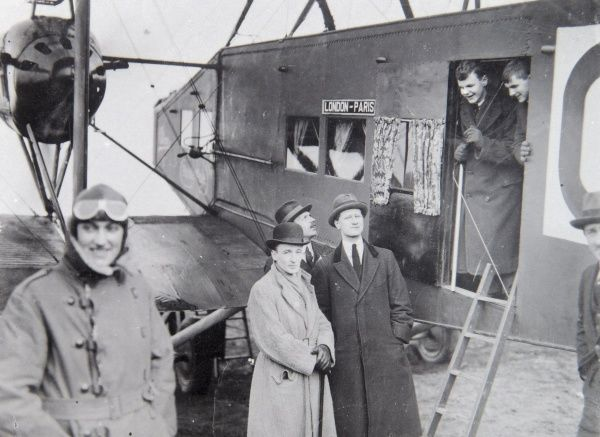 A group of passengers with an aircraft taking them on a London to Paris flight, in the early days of aviation. The pilot stands on the left, with his goggles up on his forehead