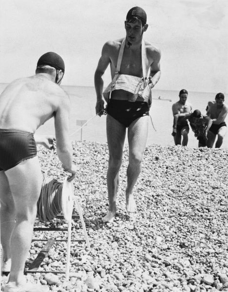 A team of Lifeguards in action on the beach at Eastbourne, Sussex, England, showing the safety equipment used to reel in the guards themselves during a rescue. Date: 1960s