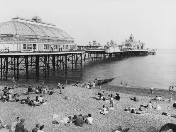 Holidaymakers and day trippers on the beach at Eastbourne, Sussex, England, beside Eastbourne Pier
