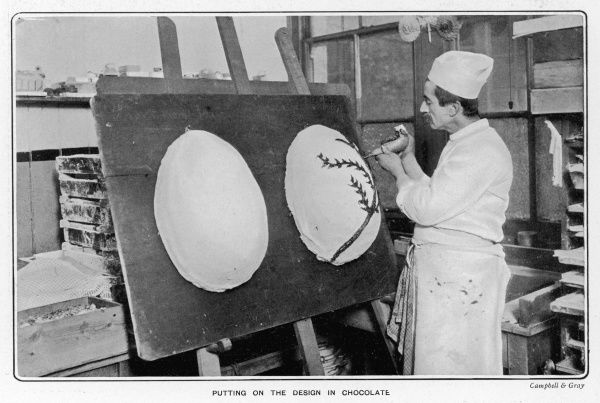 Photograph showing a worker at Fuller's Confections decorating a large chocolate Easter Egg in 1904