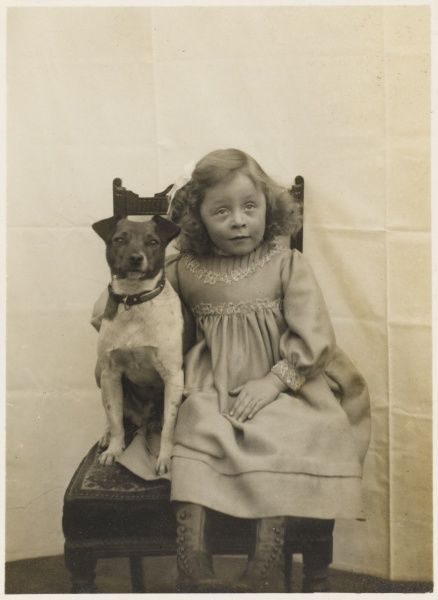 A little girl poses for her photograph with her pet Jack Russell