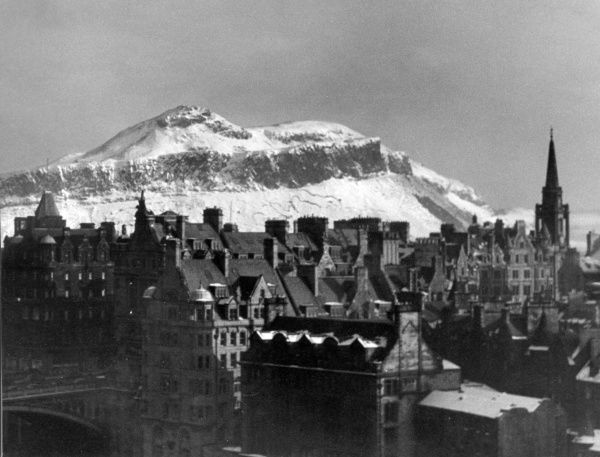 A telephoto view, form the Scott Monument, Edinburgh, Scotland, showing the view across the rooftops, Tron Church on the right and the snowy Arthur's Seat above. Date: 1960s