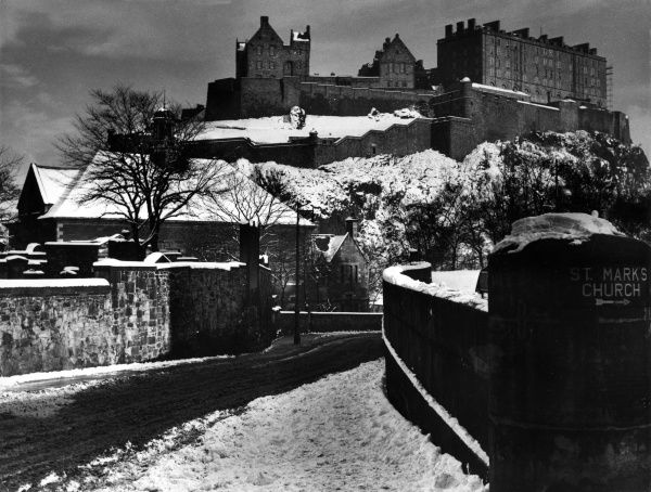 A view of Edinburgh Castle, Midlothian, Scotland, mantled in snow, as seen from Lothian Road, looking down King's Stables Road, in the foreground. Date: 1960s