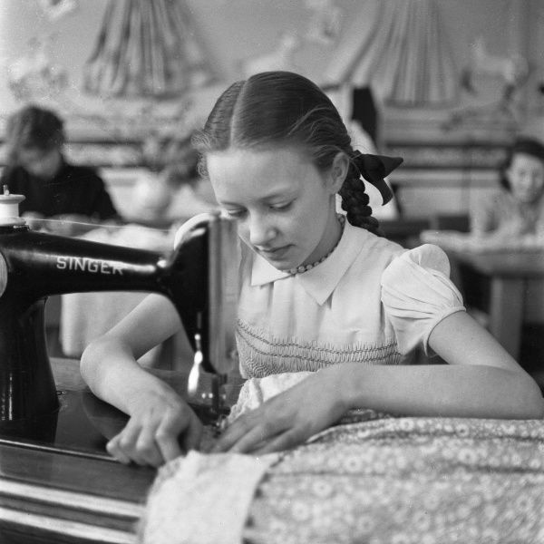 A young girl sits at a Singer sewing machine to hem a skirt during a needlework lesson at school