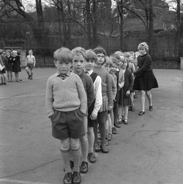 A junior prefect lines up a group of infants in the school playground