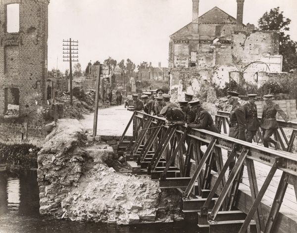 Edward, Prince of Wales (the future Edward VIII), with his father, King George V, and others, inspecting a ruined bridge in Peronne, France, during the First World War. Date: 1917