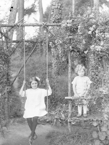 Two Edwardian children in a garden in Mid Wales. The girl on the left sits on a swing which is suspended by ropes from a wooden pole