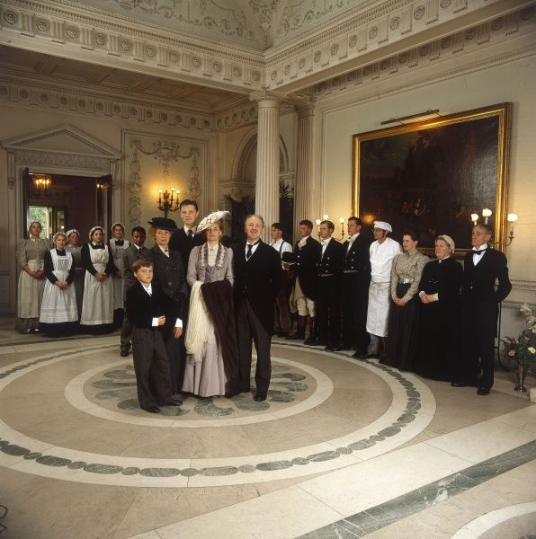 An Edwardian aristocratic family, standing in the ornate entrance hallway of their country mansion, with their many servants lined up behind them. Date: early 1900s (re-enactment)