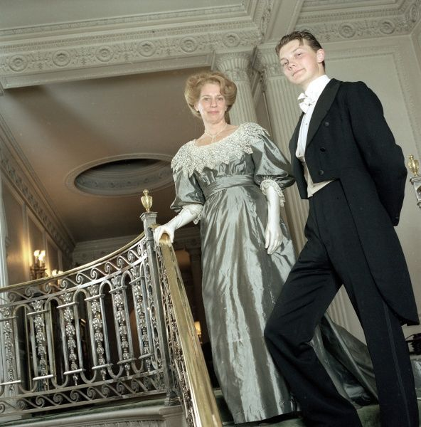 An upper class Edwardian couple on the staircase of their house, the man in a dinner suit and the lady in a silver silk evening dress