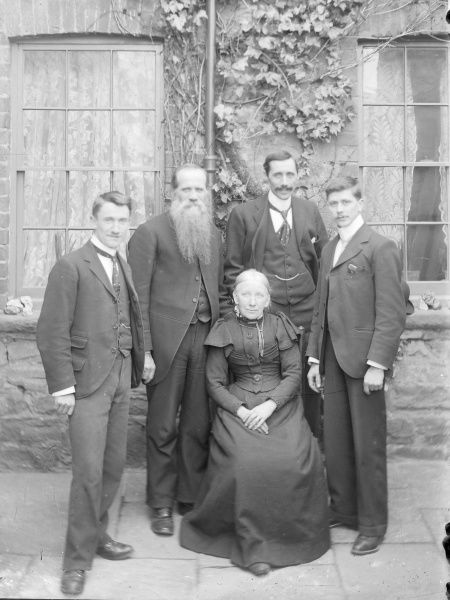 An Edwardian family group of four men and an elderly woman. One of the men (possibly the woman's husband) has a very long beard. They are in a paved area in front of a building