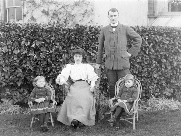 A middle class Edwardian family (parents and two daughters) pose for a photograph in their garden, probably in the Mid Wales area. Mother and daughters are sitting on wickerwork chairs. The little girls are wearing identical dresses
