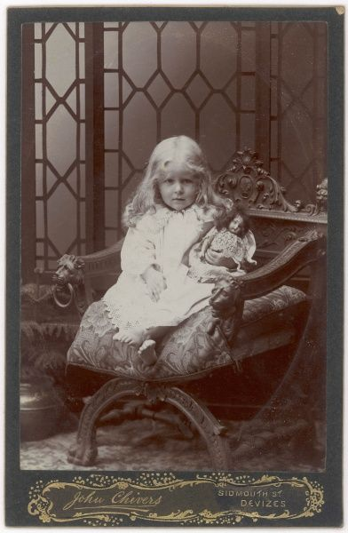 An Edwardian girl sits in an ornate wooden chair holding her doll