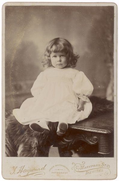 An Edwardian girl sits on a table. She is wearing a voluminous white dress