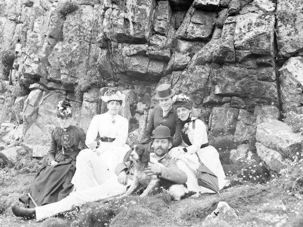 An Edwardian group at the seaside (four women and one man), sitting in front of some rocks. The man is holding a dog, which seems eager to go racing off