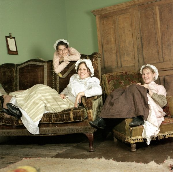 Three pretty young Edwardian housemaids larking about during a rare rest period