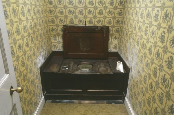 A late Victorian or Edwardian latrine, boxed into a room decorated with patterned yellow wallpaper