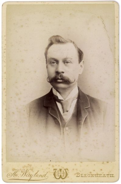 An Edwardian middle aged man with an impressive moustache in a head and shoulders studio portrait