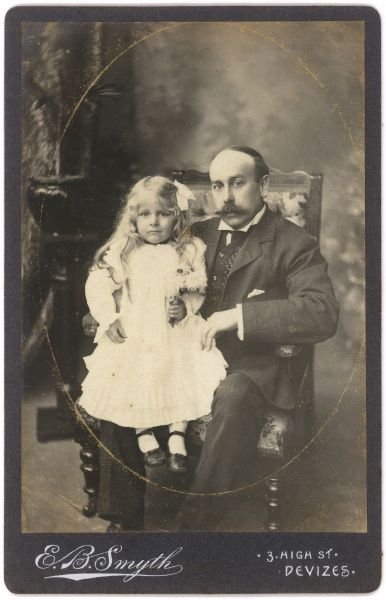 An Edwardian middle aged man sitting in a chair with a little girl in a white dress perched on his knee
