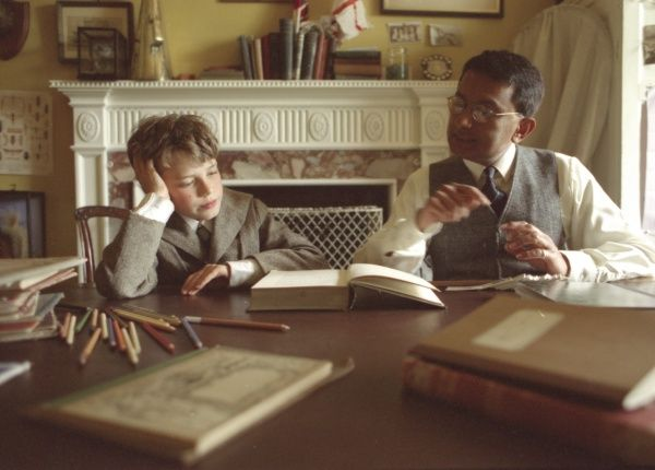 The tutor of an Edwardian teaches the Young Master in the schoolroom of his home