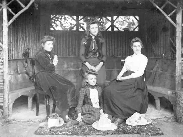 Four Edwardian sisters pose for their photo in a rustic gazebo, probably in a garden in Mid Wales