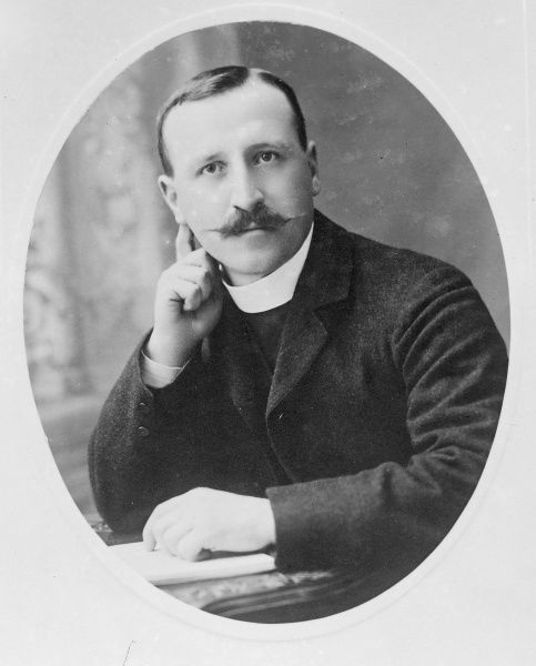 An Edwardian vicar in an oval-shaped head and shoulders portrait, Mid Wales. He is sitting at a desk with a book under his hand