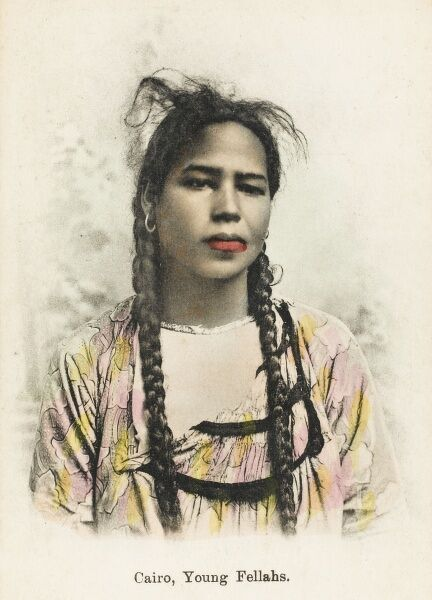 Egypt - Head and shoulders portrait of a young Native Girl of the Fellah Tribe with Pigtails, bright red lips and hooped earrings