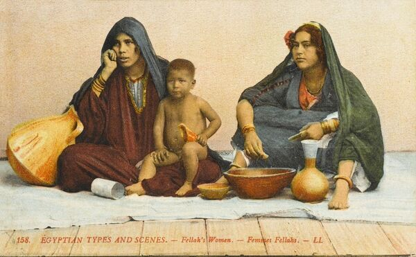Two seated Egyptian peasant women and young toddler, seated on a pale blue cloth, resting having something to eat