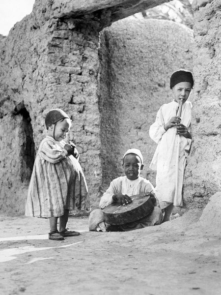 Three children playing musical instruments on the street in Egypt. Date: 1930s