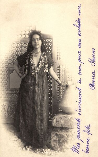 Egyptian Woman in a loose robe with fine necklaces and standing with her hand on a large broken-topped amphora (possibly deliberately so?). Date: 1901