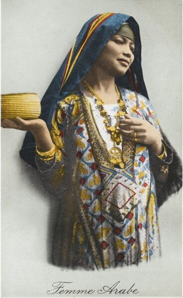 Egyptian woman in colourful costume, with gold necklace and a patterned dress. In one hand she holds a small round bowl