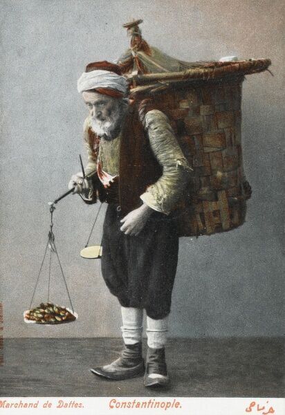 An elderly date seller - Constantinople, carrying a fine set of metal scales. He also carries a large wicker basket on his back