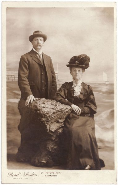 An elderly Edwardian couple pose for their photograph in the studio, with a large lump of rock to lean on, and a seaside painted backdrop. He is wearing a smart three-piece suit and trilby hat. She is wearing a dark dress with white lace at the neck
