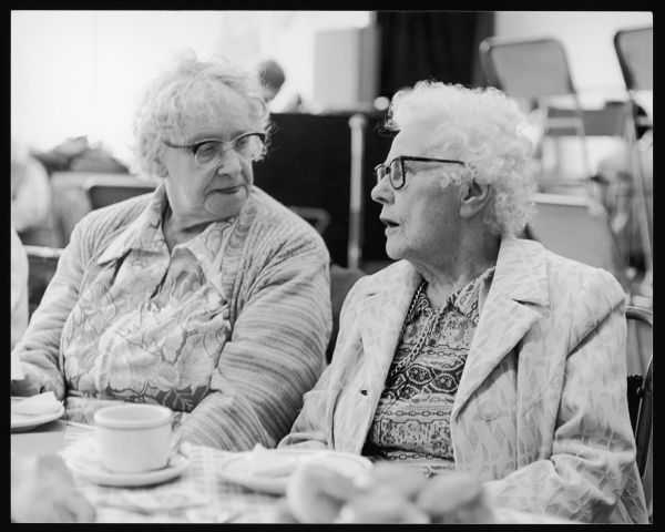 Two elderly ladies chat at a pensioners' tea party