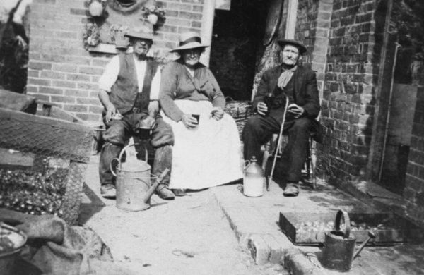 Three elderly people, two men and a woman, sitting outside their home, enjoying a glass of beer and a bite to eat