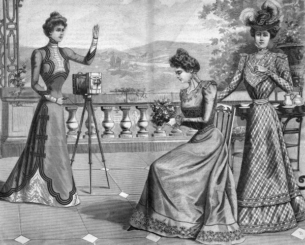 One well-dressed woman takes a photograph of two others, recording their fashionable dresses for their grandchildren to marvel at Date: 1899