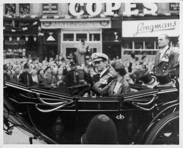 ELIZABETH II With her husband, Philip Duke of Edinburgh, waving to crowds from an open carriage