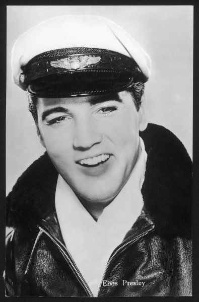 ELVIS PRESLEY American pop singer, guitarist and actor in musical films, seen here in a leather jacket and peaked cap