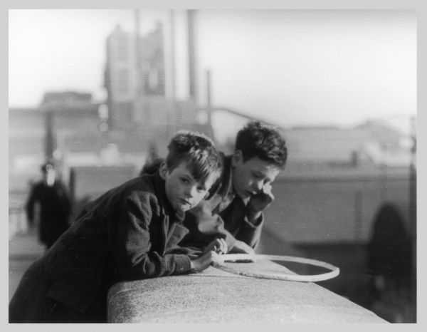 Two boys leaning against the Embankment wall, London