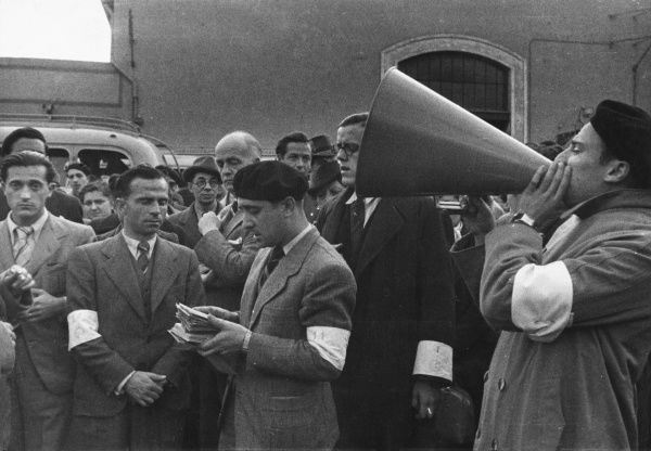 During World war II, representatives of the National Joint Committee for Spanish Relief (in armbands) went through the identity papers and lists of emigrants and called out their names one by one using a megaphone