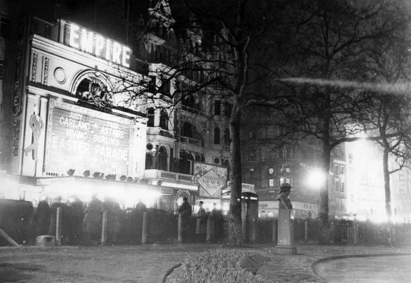 The Empire cinema in Leicester Square, London, at night, showing Easter Parade with Judy Garland and Fred Astaire. The Monseigneur News Theatre is next door. Date: 1948