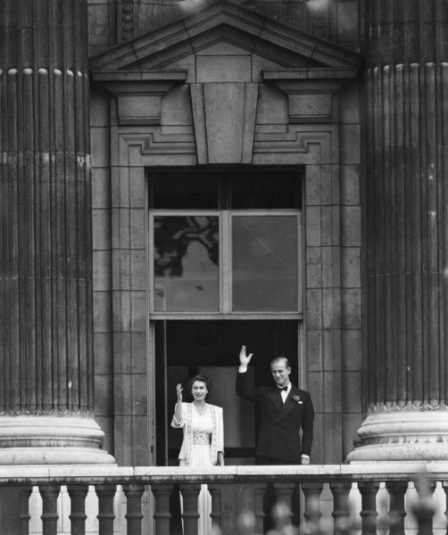 A long focus picture showing the future Queen Elizabeth II together with her fiance, Lieutenant Philip Mountbatten, waving to crowds from the balcony of Buckingham Palace following the announcement of their engagement in July 1947. Date: 1947